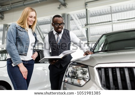 Sales consultant shows the girl a new car to buy
