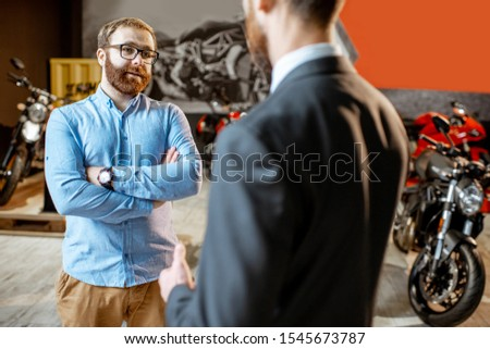 Sales consultant with a client choosing sports motorcycle to buy in the showroom