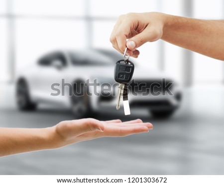 Sales executive giving car key closeup with car in background