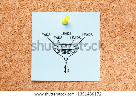 Sales funnel lead generation business concept drawn on blue sticky note pinned on cork bulletin board.