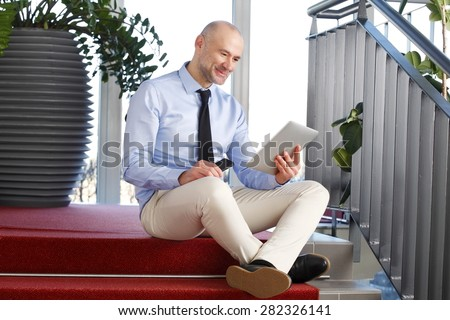 Sales man sitting at staircase while reading on digital tablet and holding his handy.