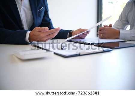 Sales manager giving advice application form document, considering mortgage loan offer for car and house insurance