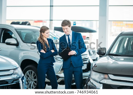 Sales managers of a car showroom standing and looking at clipboard #746934061