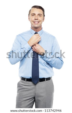 Sales representative adjusting his tie before the meeting. Looking at camera