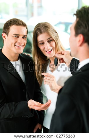 Sales situation in a car dealership, the dealer is handing auto keys to a young couple, they are excited, cars standing in the background