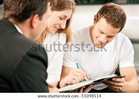 Sales situation in a car dealership, the young couple is signing the sales contract to get the new car in the background