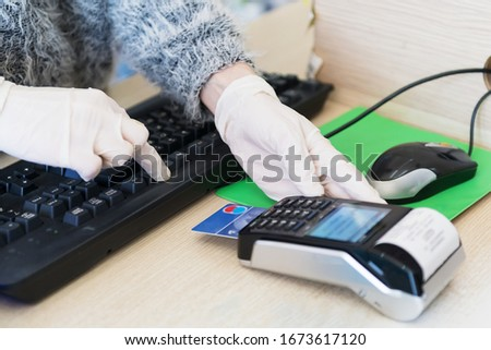 Salesewomen in gloves Respecting health standards during the pandemia of Coronavirus, insert la credit card in card reader, payment, buy and sell products and service