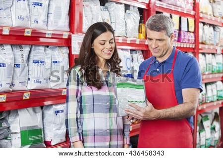 Salesman Assisting Customer In Buying Pet Food At Store