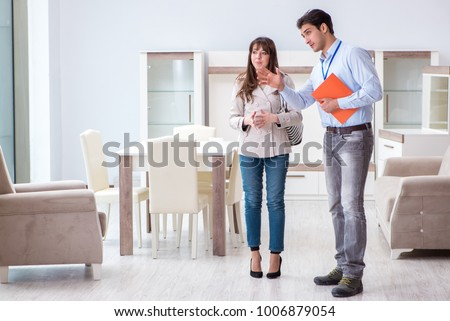 Salesman explaining to woman customer at furniture store #1006879054