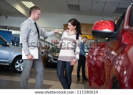 Salesman giving car keys to a woman in a car shop