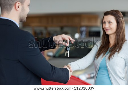 Salesman giving car keys while shaking hand of a woman in a garage