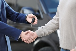 Salesman giving key to customer while shaking hands in modern auto dealership, closeup. Buying new car