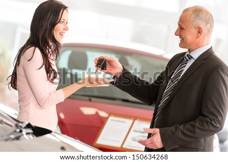 Salesman handing car keys to smiling woman