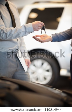 Salesman handing keys to a customer in a car shop - stock photo