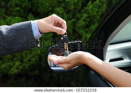 Salesman handing over the keys to a new car. Closeup of the man's hand handing keys to the woman's hand sticking out the window of the vehicle.