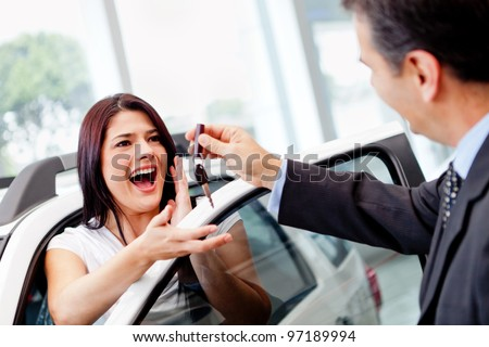 Salesman handling keys to a woman after buying a car