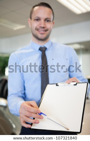 Salesman holding a contract in a dealership - stock photo