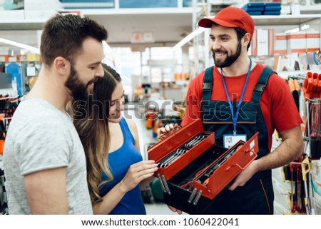 Salesman in red shirt and baseball cap is showing couple of clients new toolbox in power tools store.