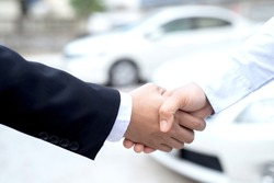 Salesman is carrying the car keys delivered to the customer at the showroom with a low interest offer. Special promotion