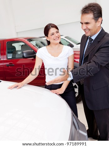 Salesman showing cars to a woman for her to buy
