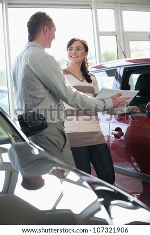 Salesman showing documents ta a woman in a car shop
