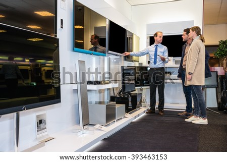 Salesman showing flat screen TV to young couple in electronics store