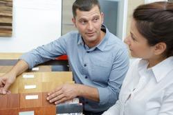 salesman showing wood flooring samples to customer