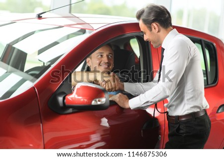 Salesman shows car options for client. Client sitting in the car. Car is red. They are in car dealership.