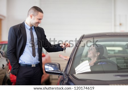 Salesman smiling while giving keys to a woman in a car dealership