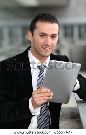Salesman standing oustide with electronic tablet