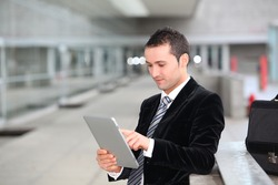 Salesman stannnding oustide with electronic tablet