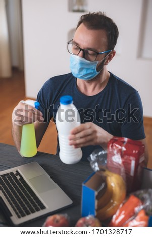 Salesman sterilizing food prepared for order over the internet during the virus outbreak worldwide. Shopping / buying / ordering groceries and food remotely using laptop and internet.