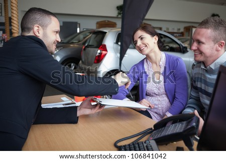 Salesman talking to a couple in a car shop
