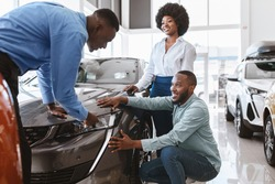 Salesman talking to young black couple, showing them new luxury car at auto dealership. African american clients buying or renting automobile at showroom. Vehicle local distribution concept