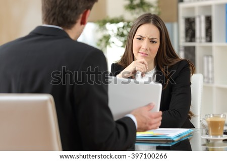 Salesman trying to convince a doubtful customer showing products in a tablet at workplace