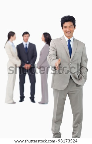 Salesman with team behind him offering hand against a white background