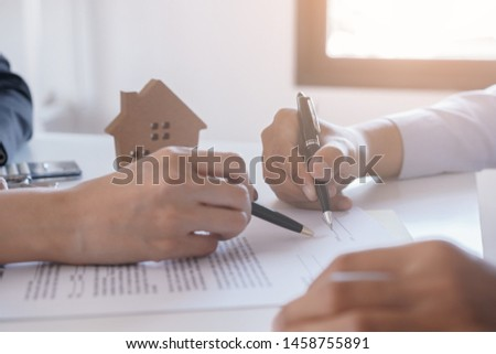 Salesmen are letting the male customers sign the sales contract, Asian women and men are doing business in the office, Business concept and contract signing #1458755891