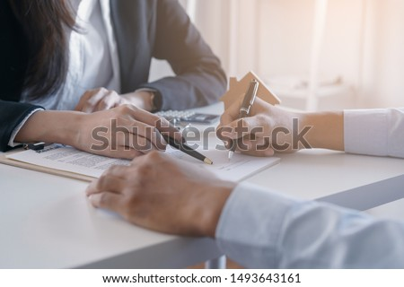 Photo of  Salesmen are letting the male customers sign the sales contract, Asian women and men are doing business in the office, Business concept and contract signing