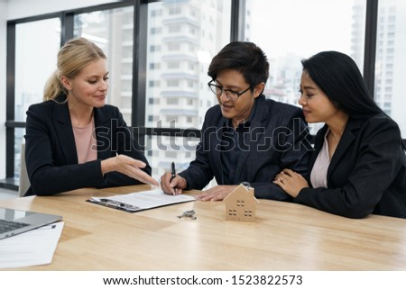 Salesmen are letting the male customers sign the sales contract, caucasian women and couple are doing business in the office, Business concept and contract signing #1523822573