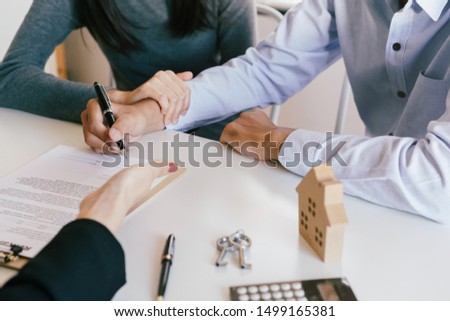 Salesmen are letting the male customers sign the sales contract house, Asian women and couple are doing business in the office, Business concept and contract signing	 #1499165381