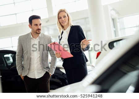 Salesperson selling cars at car dealership