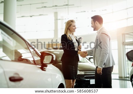 Salesperson selling cars at car dealership #585608537