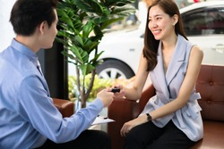 Salesperson workin at car dealership.Young Asian male consultant and couple buyers signing contract for new car in auto show. Concept for car rental or sale .Payment bt credit card.