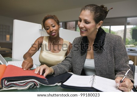 Saleswoman Assisting Customer With Swatches