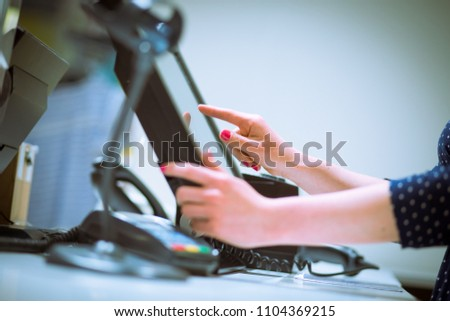 Saleswoman doing process payment on touchscreen pos, counting sale