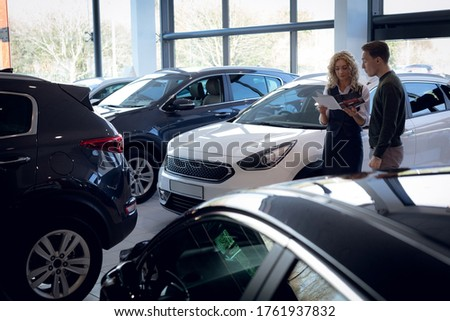 Saleswoman reading brochure while standing by customer in car showroom