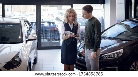 Saleswoman showing brochure to customer while standing by cars in showroom