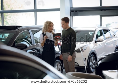 Saleswoman showing brochure to male customer while standing by cars in showroom
