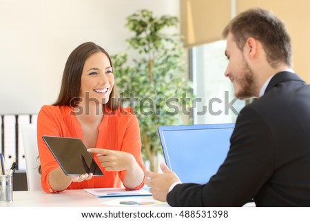 Saleswoman trying to sell products to a client showing them in a tablet at office