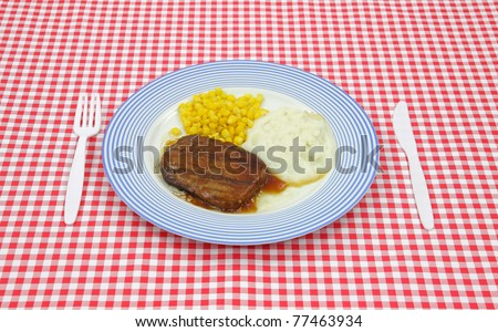 Salisbury steak meal with corn and potato on a blue striped plate with plastic silverware on a red checkerboard cloth.
